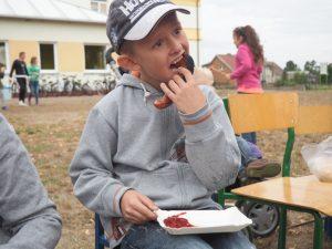 chłopiec je kiełbaske