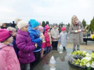 dzieci stoją z panią przy grobie patrona